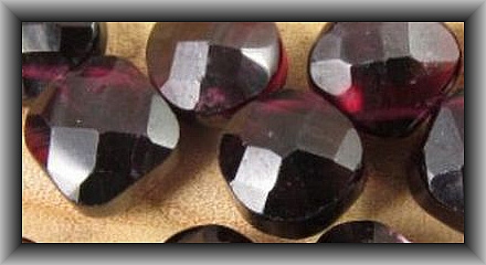 Most stones cut in India are dyed. It is almost an industry standard. This is a garnet which is a stone often cut in India so .... usually dyed.